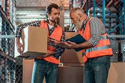 two men in warehouse reviewing inventory